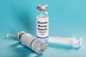 70455280 - measles mumps rubella vaccine vials with syringe over turquoise background: Copyright: andreypopov / 123RF Stock Photo